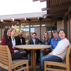 Mike McCusker, Katie Ha, members of the Teaching and Learning Center staff, and students sit in the courtyard of the Teaching and Learning Center